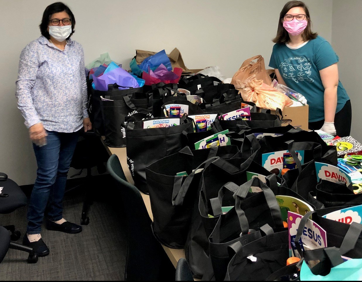 Two light-skinned women in surgical masks stand next to a table covered in care packages and supplies.